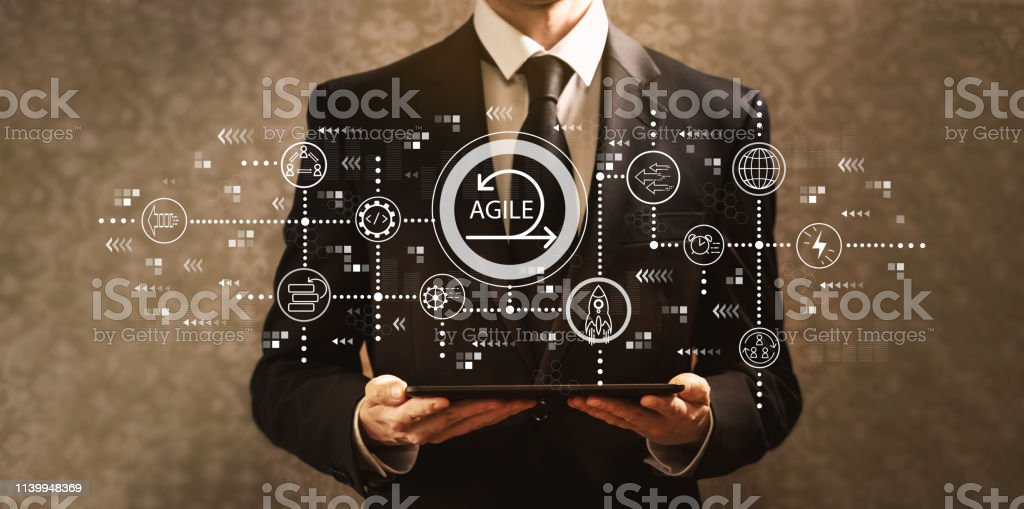 Agile concept with businessman holding a tablet computer Agile concept with businessman holding a tablet computer on a dark vintage background Adult Stock Photo