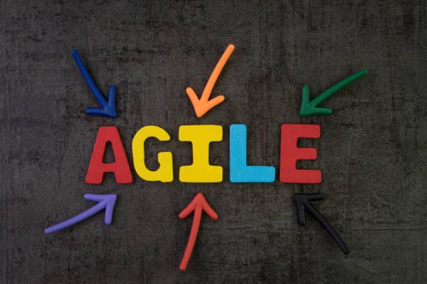 agile entwicklung, neue methodik zur software, idee, workflow-management-konzept, multi color pfeile auf das wort agile in der mitte der schwarzen tafel betonmauer, schnell und flexibel - mobilität stock-fotos und bilder
