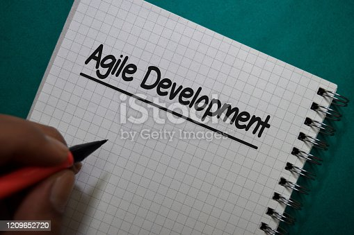844020228 istock photo Agile Development write on a book isolated on Office Desk 1209652720