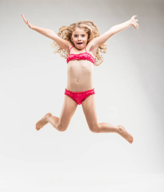 agile exuberant little girl leaping in the air - girl alone in swimsuit stock photos and pictures