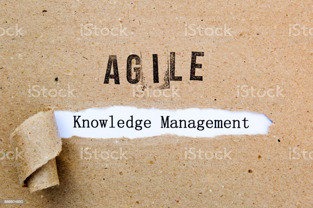 Agile Knowledge Management - printed text underneath torn brown paper with Agile printed in ink stock photo