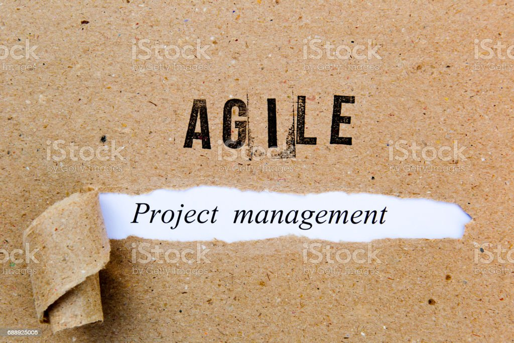 Agile Project Management - printed text underneath torn brown paper with Agile printed in ink stock photo