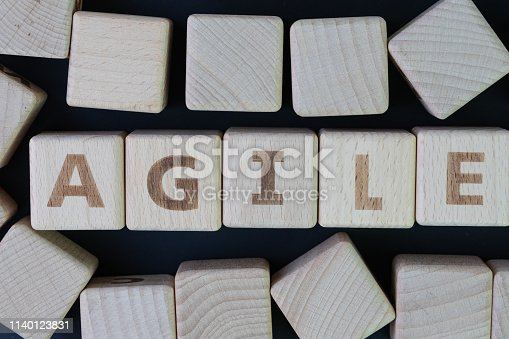 istock Agile software development concept, cube wooden block with alphabet building the word Agile at the center on dark blackboard background, requirements and solutions evolve through collaborative effort 1140123831