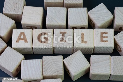 952856170 istock photo Agile software development concept, cube wooden block with alphabet building the word Agile at the center on dark blackboard background, requirements and solutions evolve through collaborative effort 1147226205