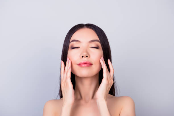 Aging, acne, pimple, wrinkles, oily, dry skin concept. Close up photo of pretty young korean lady, touching her cheeks and look happy stock photo