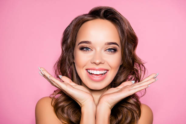 Aging, acne, pimples, wrinkles, oily, dry skin concept. Close up cropped photo of pretty excited lady with wavy hairdo, arm palms near face, happiness and freshness, purity – zdjęcie