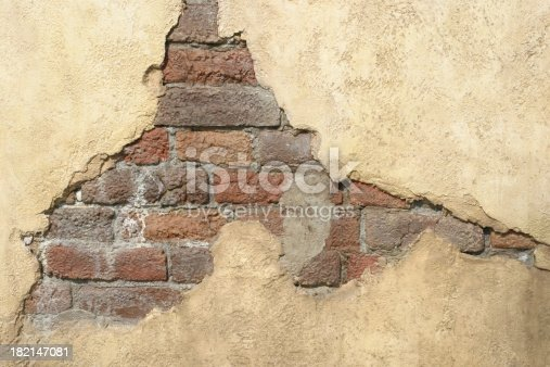 Old wall with bricks showing through the surface.