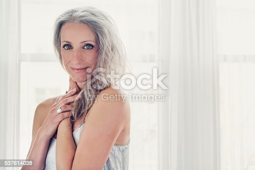 Aging gracefully, portrait of beautiful mature woman with silver hair and silver dress. Studio shot with natural light. Natural and sensual, she is standing up, bare shoulders, ready to dance with a party sequin dress. She is looking straight at camera with a smile. Horizontal waist up shot with copy space. Window in background. This was taken in Quebec, Canada.