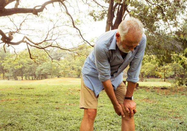 homem do envelhecimento que tem a dor em seu joelho no parque, dor nos idosos, cuidados médicos - articulação humana - fotografias e filmes do acervo