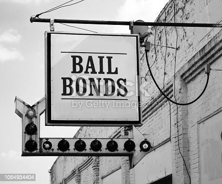 A rusty white bail bonds sign needs bulbs replaced but still points at the office entrance