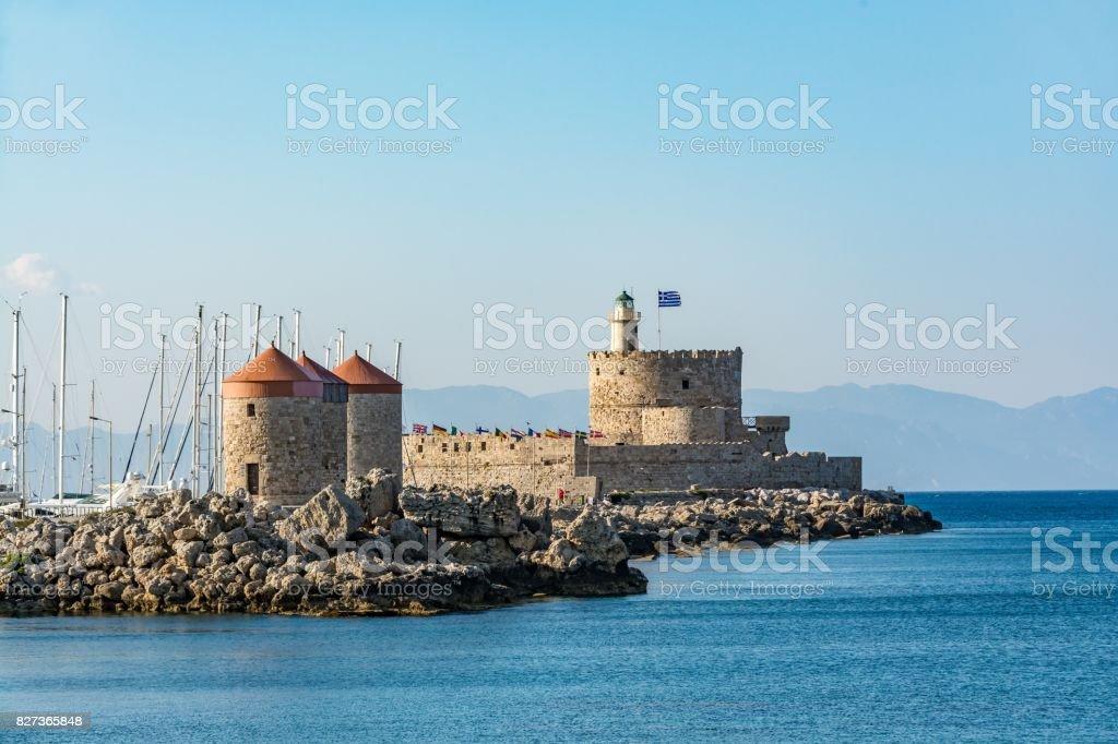 Agios Nikolaos Fort (Fort of Saint Nicholas) and mills, at the entrance to Mandraki harbor, Rhodes island, Greece stock photo