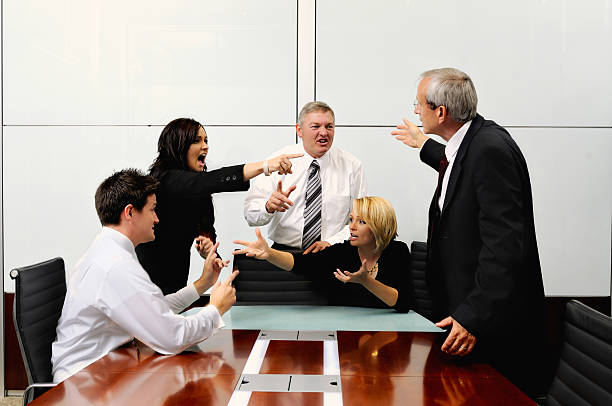 Agitated business people at a meeting pointing at each other stock photo