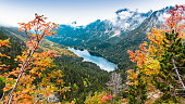 A distant lake surrounded by mountains, clouds and trees at autumn, \