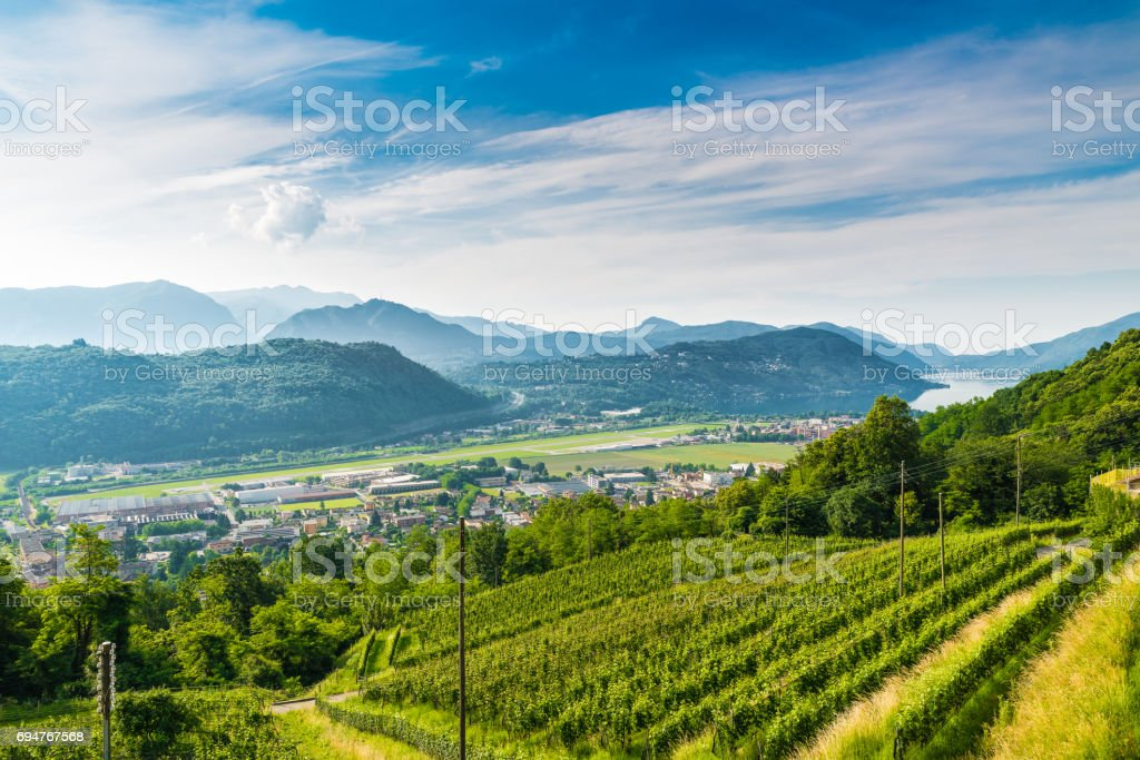 Agno, Canton Ticino, Switzerland. View of Agno, Lake Lugano, Lugano Airport, vineyards on the hills surrounding, on a beautiful summer day stock photo