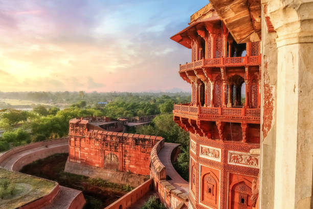 Agra Fort exterior architecture with landscape at sunset Agra Fort - Famous medieval historic fort exterior structure with view of Agra city landscape at sunrise agra stock pictures, royalty-free photos & images