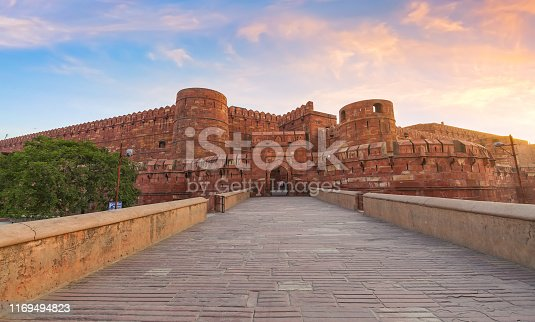 Agra Fort - Historic red sandstone fort of medieval India also known as the Red Fort Agra at sunrise. Agra Fort is a UNESCO World Heritage site in the city of Agra India.