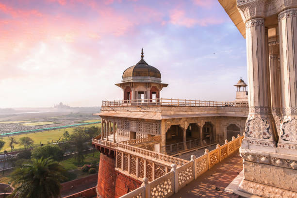 Agra Fort - Medieval Indian fort made of red sandstone and marble with view of dome at sunset. Agra Fort is a historical fort in the city of Agra in India being the main residence of the emperors of the Mughal Dynasty until 1638. View of the Musamman Burj dome of Agra Fort with view of Taj Mahal at the horizon agra stock pictures, royalty-free photos & images