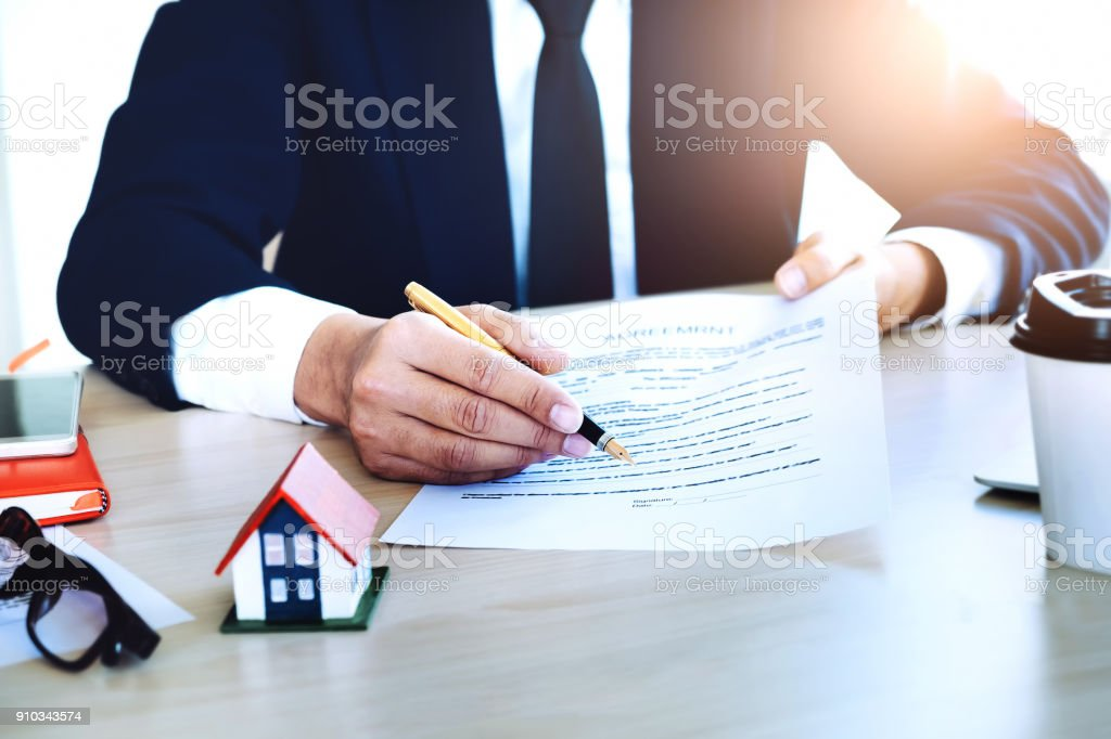 agreement paper,estate agent gives pen and documents agreement with customer to sign contract for . Concept insurance stock photo