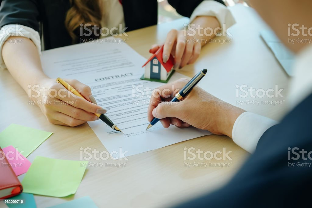 Agreement paper,estate agent gives pen and documents agreement with...