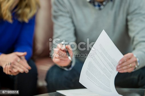 A Caucasian heterosexual couple are sitting in the living room of their newly-purchased house. They are wearing casual clothing. They are looking at the mortgage contract for the house.