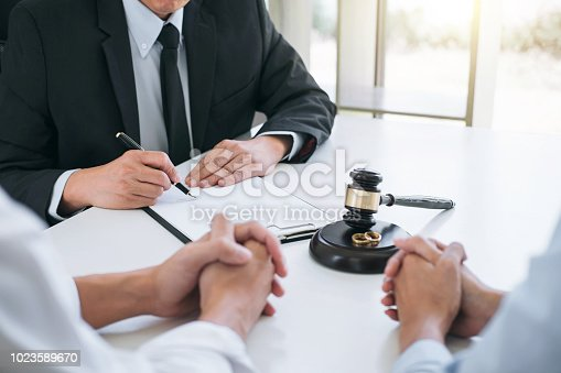 istock Agreement prepared by lawyer signing decree of divorce (dissolution or cancellation) of marriage, husband and wife during divorce process with male lawyer or counselor and signing of divorce contract 1023589670