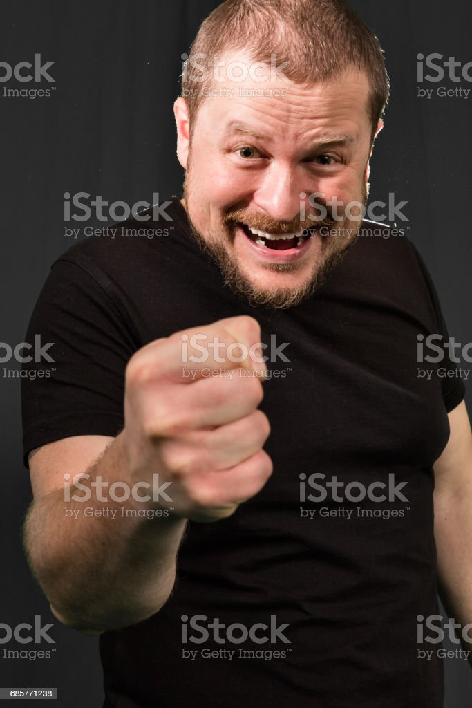 Agressive bully threatens with a fist royalty free stockfoto
