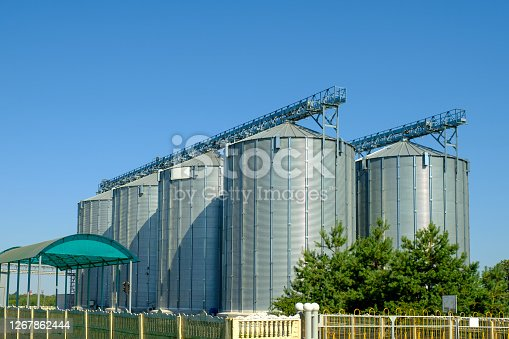 Agribusiness concept. Agro manufacturing plant for processing drying cleaning and storage of agricultural products, flour, cereals and grain. Granary elevator.