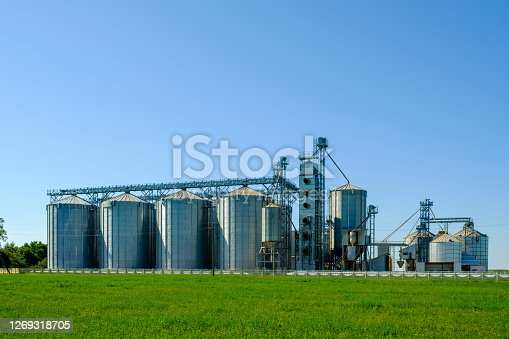 Agribusiness concept. Agro-processing and manufacturing plant with metal silos for grain storage, drying, cleaning agricultural products, flour, cereals and grain