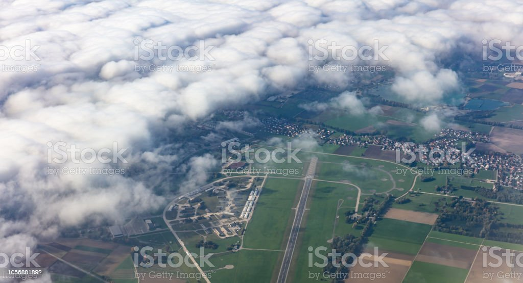 Agricultural fields and houses from above. Aerial view out of a plane...