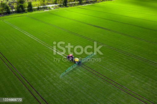 Agricultural industry, tractor spraying herbicides in green field
