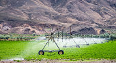 A letterbox format image of a long automated irrigation machine in use in the dry mountain landscape of Utah, USA.