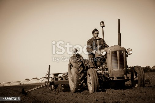 Farmer in  Old-fashioned tractor sowing crops at field, Sepia