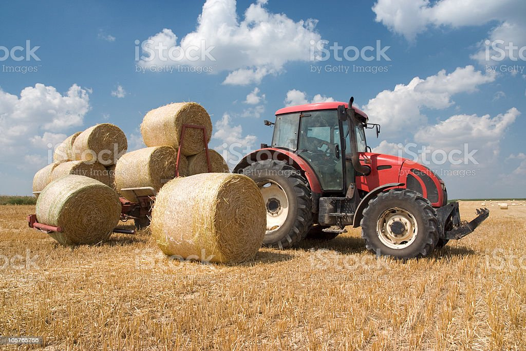 Agricultural photo of tractor moving circular hay bales royalty-free stock photo