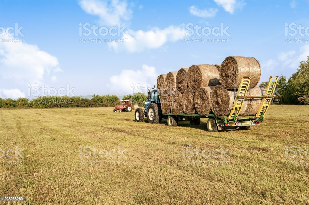 Agricultural scene. Tractor lifting hay bale on barrow. stock photo