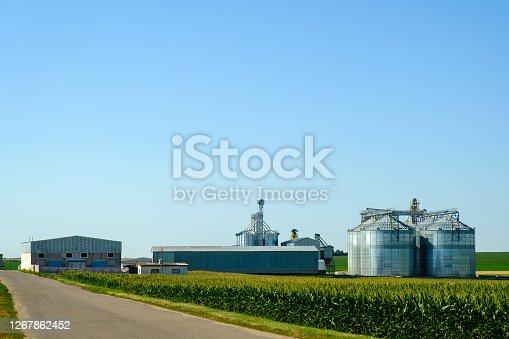 Agricultural Silos. Building for storage and drying of grains, wheat, corn. Modern granary elevator. Agribusiness concept.