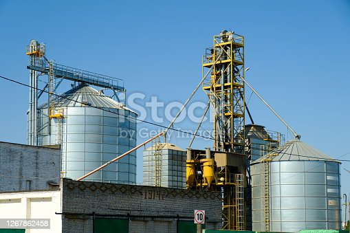Agricultural Silos. Storage tanks agricultural crops processing plant. Granary elevator. Agribusiness concept.