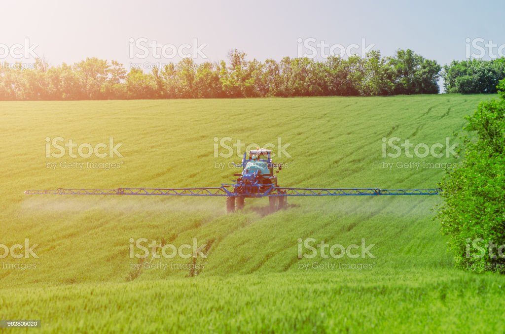 Agricultural sprayers, spray chemicals on young wheat. - Foto stock royalty-free di Accudire