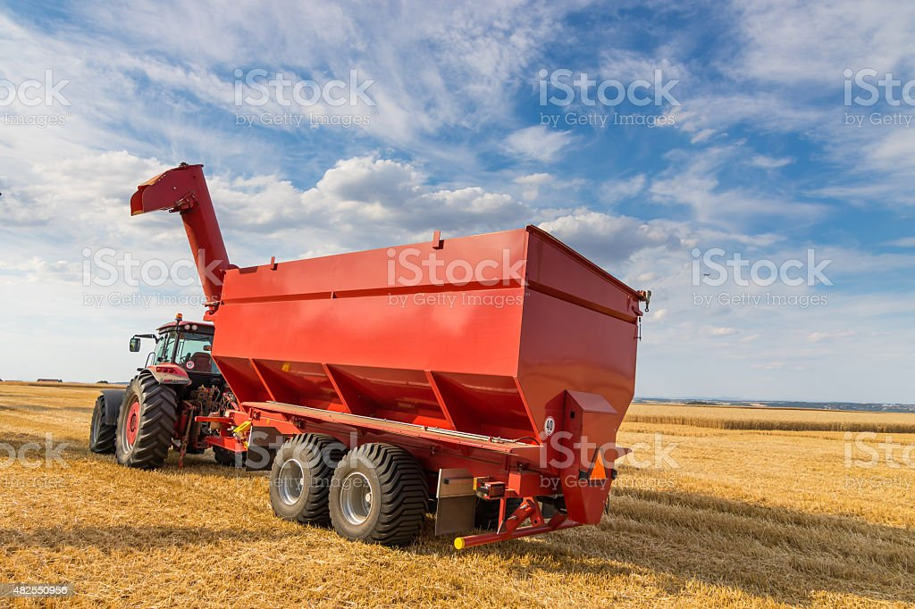 Agricultural tractor and harvesting trailer stock photo