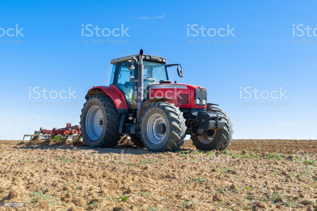 agricultural tractor in the foreground with blue sky background stock photo