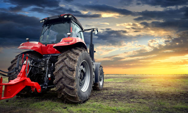 Agricultural tractor working in the field at sunset background stock photo