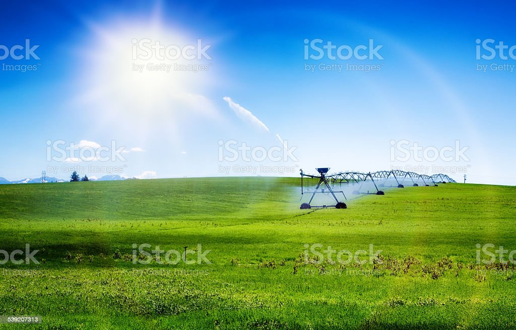 Agricultural wheeled irrigation sprinkling system with sun and lens flare stock photo