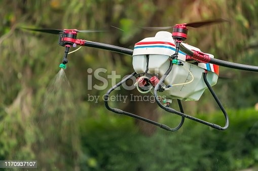 898449496 istock photo agriculture drone carry a tank of liquid fertilizer flying in the blue sky prepare to spray it in farming area 1170937107