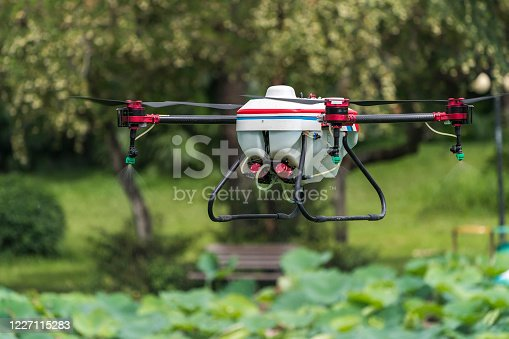 898449496 istock photo agriculture drone carry a tank of liquid fertilizer flying in the blue sky prepare to spray it in farming area 1227115283