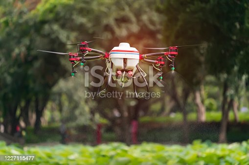 898449496 istock photo agriculture drone carry a tank of liquid fertilizer flying in the blue sky prepare to spray it in farming area 1227115477