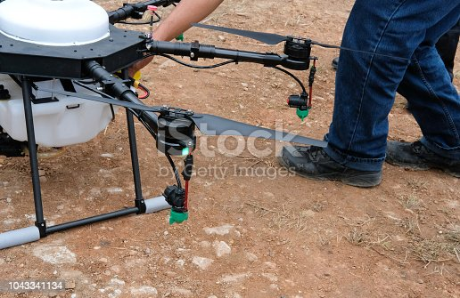 898449496 istock photo agriculture drone for spraying liquid fertilizer or herbicide in farm land. 1043341134