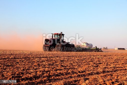 Farmer in tractor putting down anhydrous ammonia in a dusty plowed field. Horizontal image would be good for agriculture use.