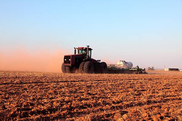 Agriculture: Farmer driving tractor with Fertilizer Tank in plowed field stock photo