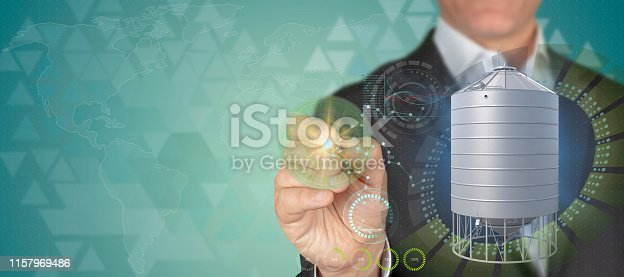 Agriculture industry concept. Businessman pointing 3D grain storage object with pen in HUD patterned techno blue background with copy space