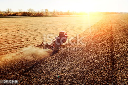 istock Agriculture machine harvesting crop in fields. Tractor pulls a mechanism for haymaking. Harvesting in autumn in the morning at dawn. agribusiness in the Altai region Russia 1051123468