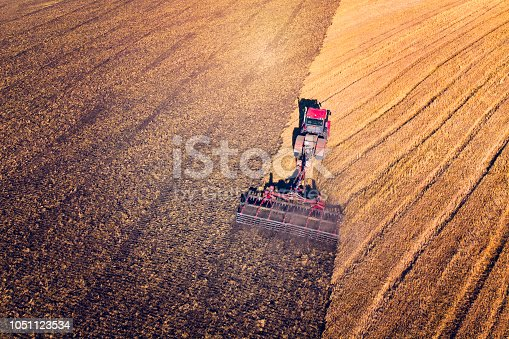 istock Agriculture machine harvesting crop in fields. Tractor pulls a mechanism for haymaking. Harvesting in autumn in the morning at dawn. agribusiness in the Altai region Russia 1051123534